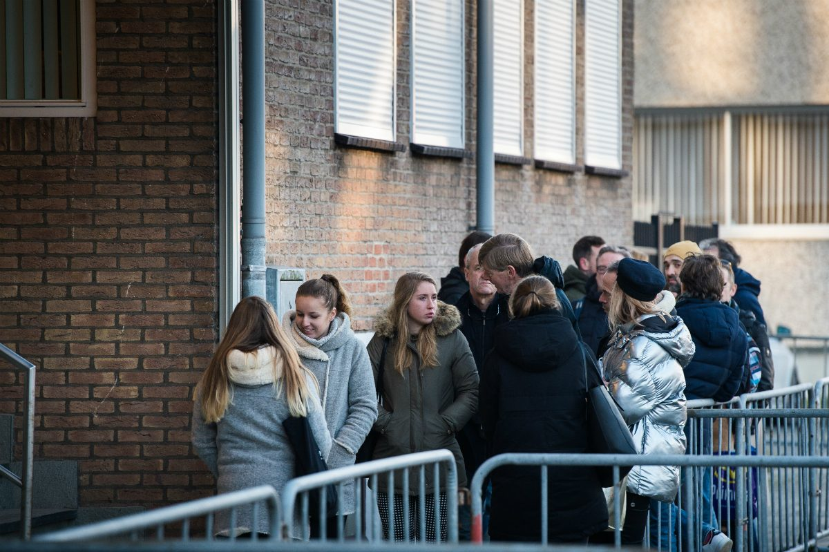 People queuing outside the high-security courthouse De Bunker to watch Astrid Holleeder give testimony against her brother Willem during his trial for murder and manslaughter.