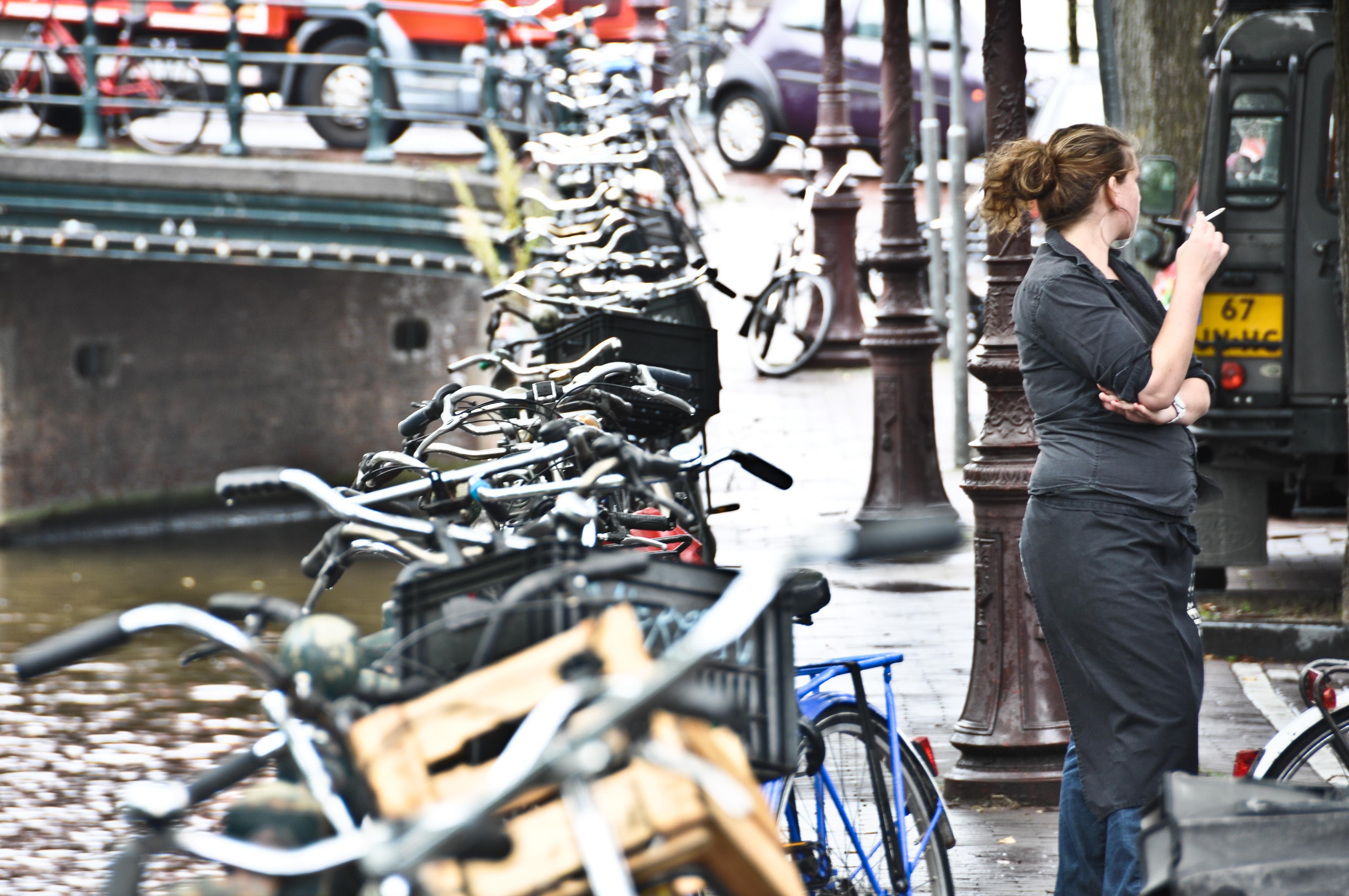 woman smoking with row of bikes