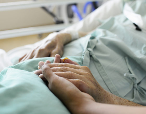A nurse and patient touch hands in a hospital.