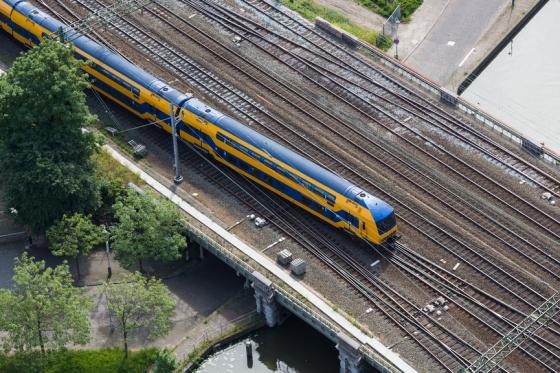 Aerial view of Dutch train at a bridge crossing a canal