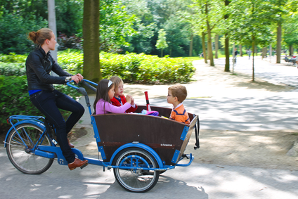 Young girl transporting children in the cart . Amsterdam. Nether