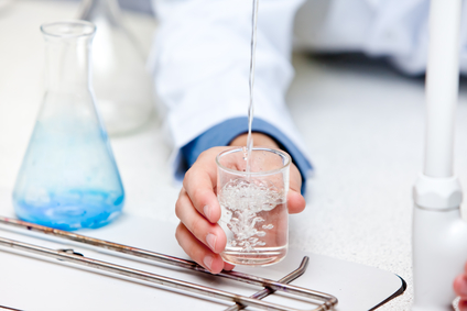 Close-up of a male scientist pouring liquid into a becher
