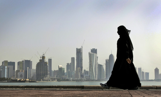 A Qatari woman walks in front of the city skyline in Doha. Photo: AP/Kamran Jebreili