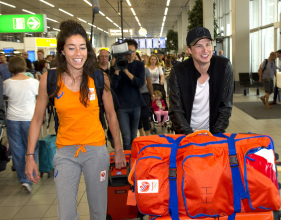 Speed skating champ Sven Kramer helps hockey player girlfriend Naomi van As with her bags at Schiphol. Photo: VI Images