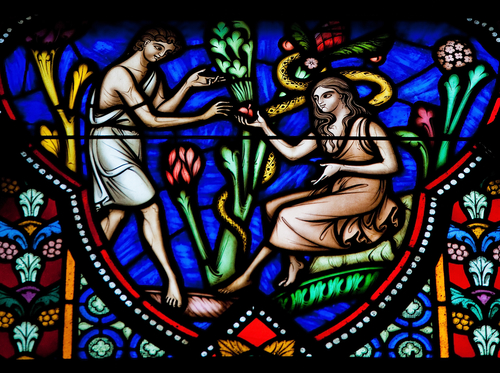 Stained glass window featuring Adam, Eve and an apple. Photo: Deposit Photos.