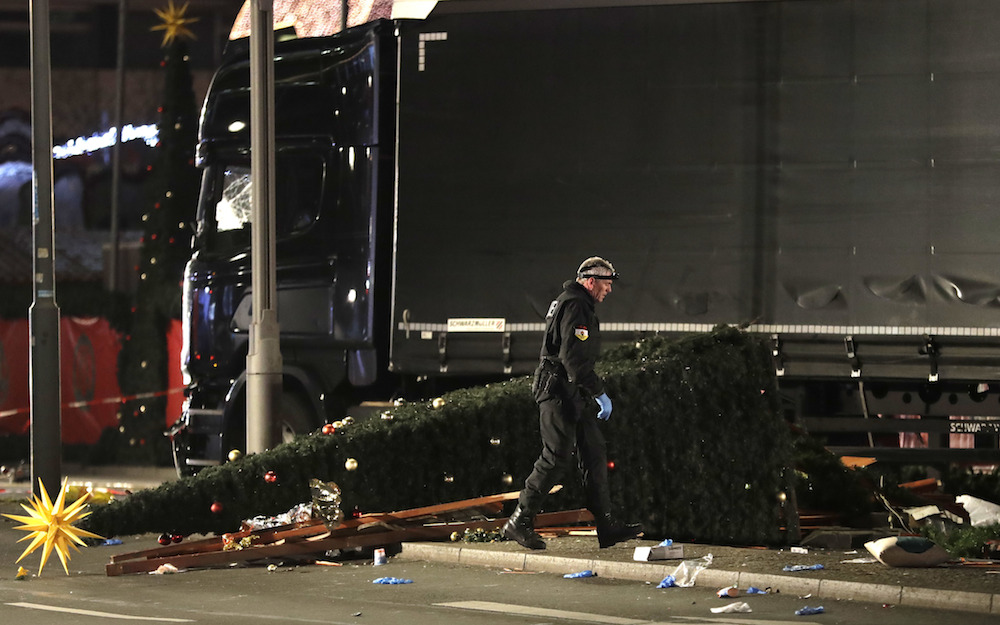 A police officer investigate the scene after a truck ran into a crowded Christmas market and killed several people in Berlin. Photo: AP Photo/Michael Sohn via HH
