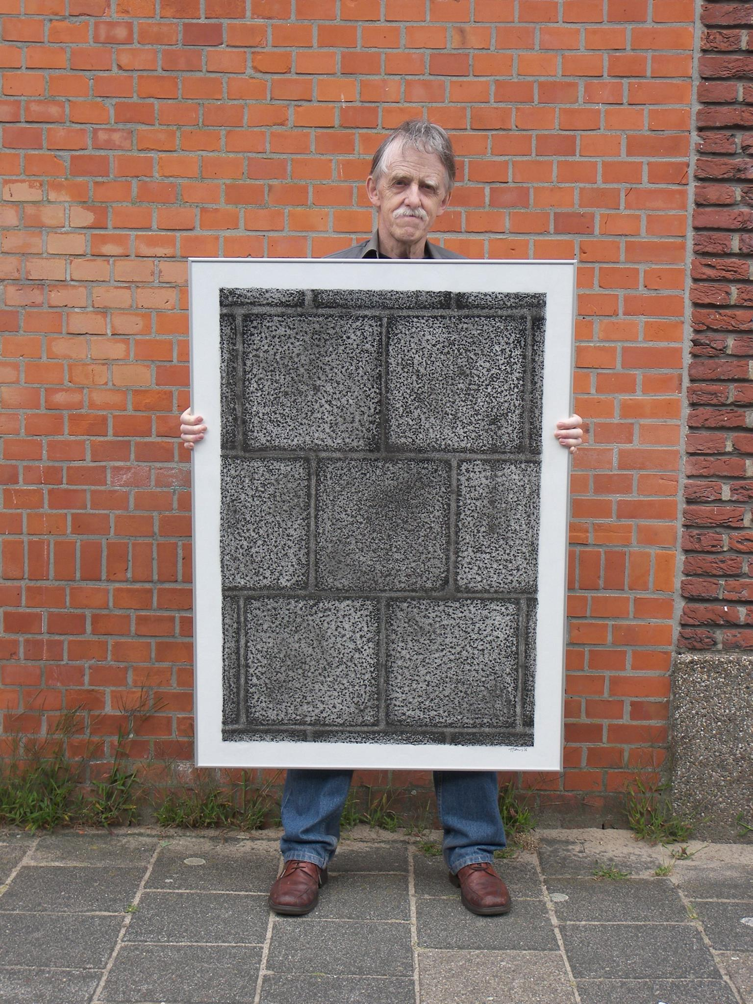 Hans Rietbergen holding up a rubbing of the paving stones where he takes pictures of people passing by his home.