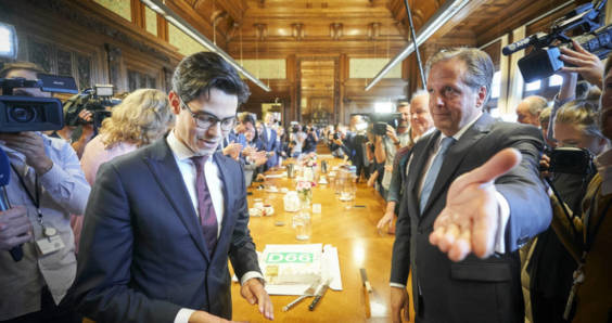 New D66 leader Rob Jetten standing next to his predecessor Alexander Pechtold, who is gesturing towards the exit of the party's conference room at the Binnenhof in The Hague.