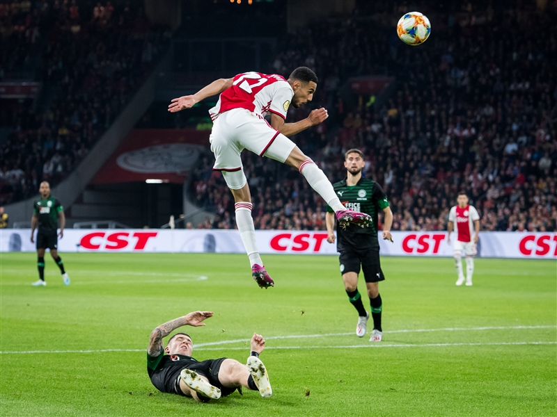 Noussair Mazraoui of Ajax leaps in the air as he is tackled by Groningen defender Django Warmerdam.