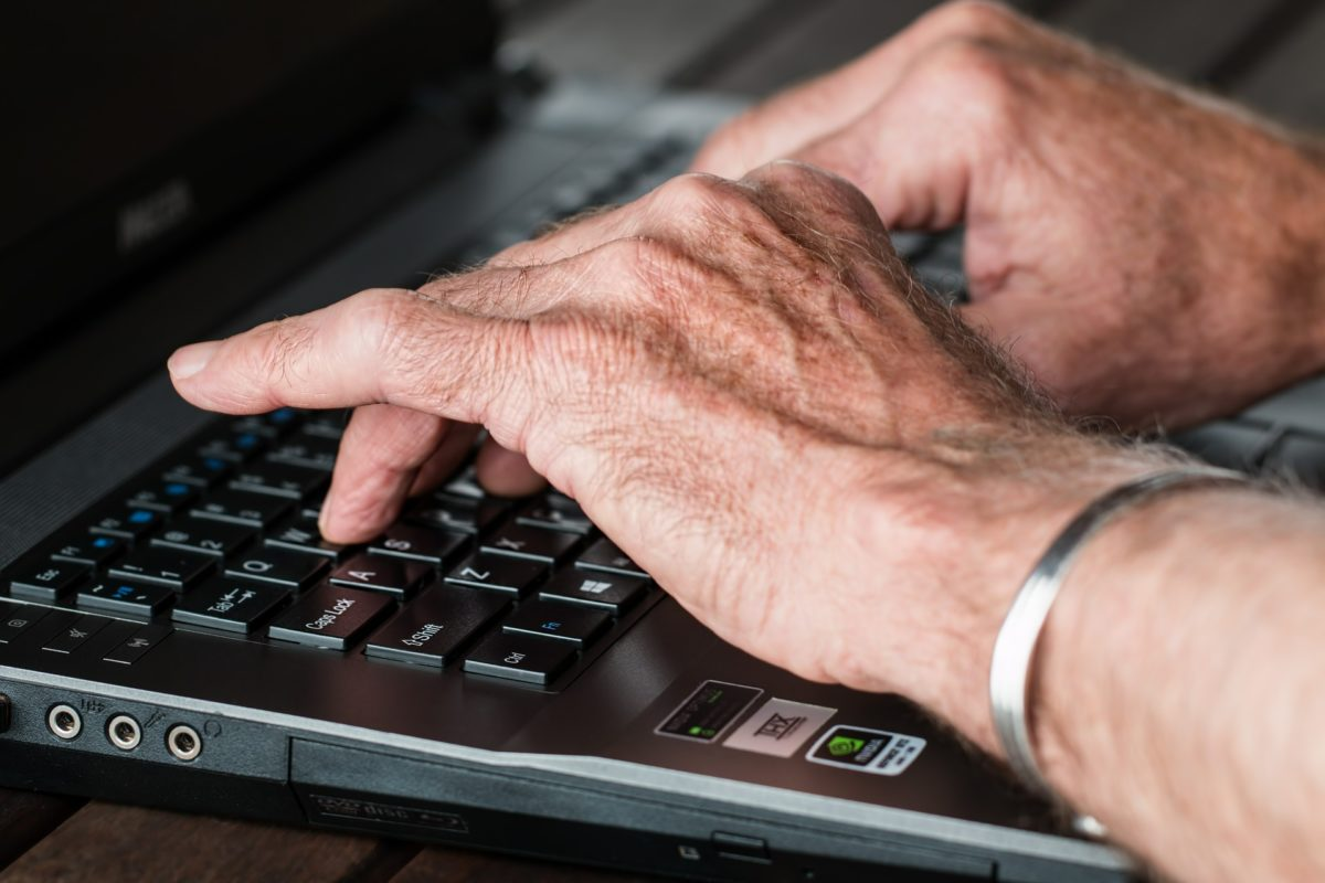 old person hands typing at a laptop in close-up