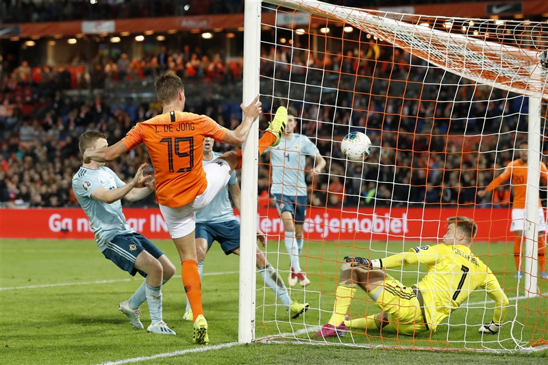 Luuk de Jong holding onto the post while scoring the decisive second goal for the Netherlands against Northern Ireland.