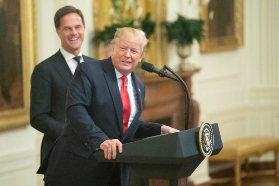Mark Rutte laughing in the background as Donald Trump leans over to the side of the White House podium.