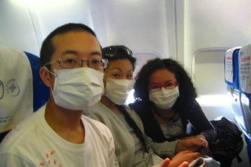 Three people in an aeroplane wearing facemasks