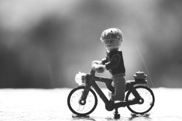 Black and white image of Lego figure on miniature bicycle