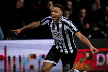 Cyriel Dessers of Heracles spreads his arms to celebrate scoring the winning goal against Ajax
