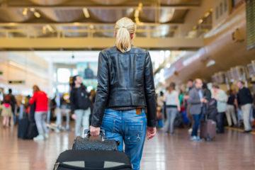 a female traveller walking through an airport pulling a trolley bag