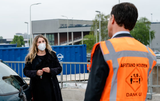 Mark Rutte speaking to a woman wearing a face mask during a site visit to The Hague's refuse collection service.