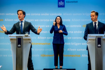 Mark Rutte, sign language interpreter Irma Sluis and health minister Hugo de Jonge on stage at a press conference