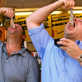 Two men eating new herring in the traditional way, by dropping it into their mouths