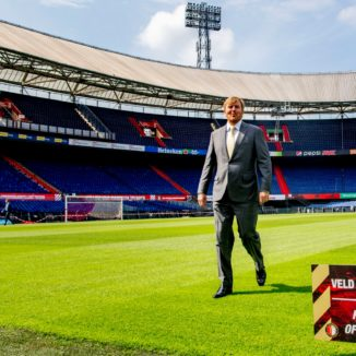 King Willem-Alexander walking on the pitch at Feyenoord past a sign saying 'keep off the grass'