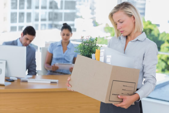 A woman carrying a box of items away from her desk in an office