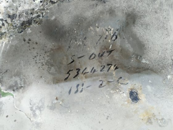 An aluminium panel with the serial number BK716 inscribed on the inside.