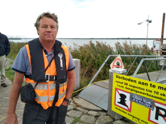 Arie Kappert in an orange life vest beside a sign at the staithe in Almere where recovered pieces of plane are landed.