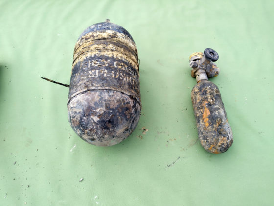 An oxygen cylinder from the wreckage laid out on a green tablecloth.