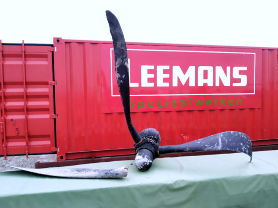 The propellor of the plane, with one blade broken off, laid out on a table in front of a red Leemans Speciaalwerken cargo container.