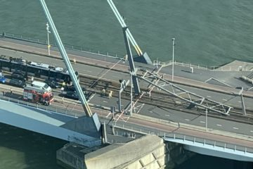 An overhead view of the bridge with the cable support lying on the ground at one end.