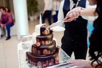 a close-up of a wedding cake coated in chocolate being sliced