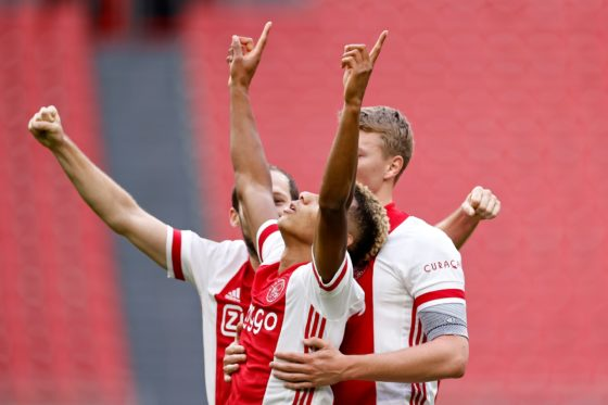 Ajax winger David Neres raises his arms as he celebrates scoring Ajax's second goal with team-mates Daley Blind and Per Schuurs.