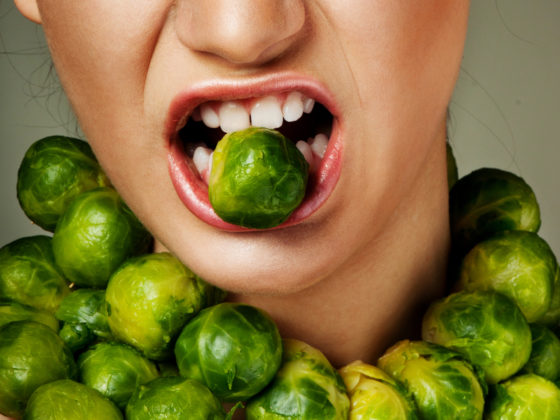 A Brussels sprout in the mouth of a woman who has more rings of sprouts around her neck