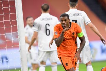 Georginio Wijnaldum smiles and points in celebration after scoring his second goal