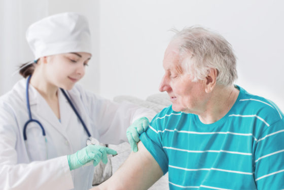 A nurse giving a vaccine to an elderly person